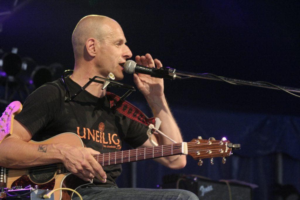 Lutz Drenkwitz auf der Bühne mit Gitarre und Mikrofon